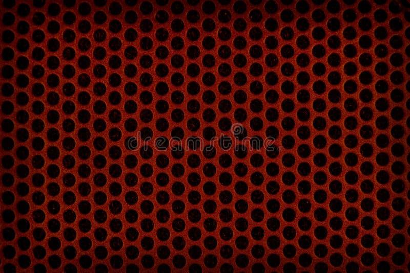 Röd perforerad plastic bakgrund royaltyfri fotografi