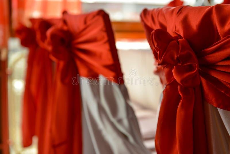 Röd pilbåge som binds på baksidan av stol arkivfoton