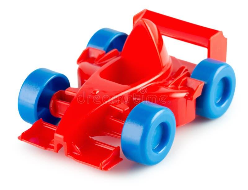 Röd plast- leksakbil som isoleras på den vita bakgrunden arkivfoton
