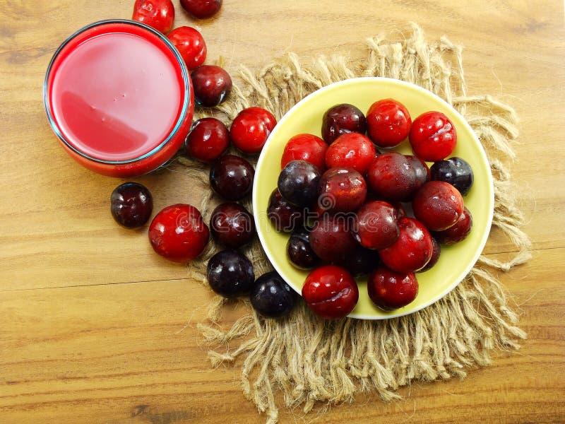 Röd plommon- och mixefruktfruktsaft på bästa sikt för träbakgrund royaltyfri foto