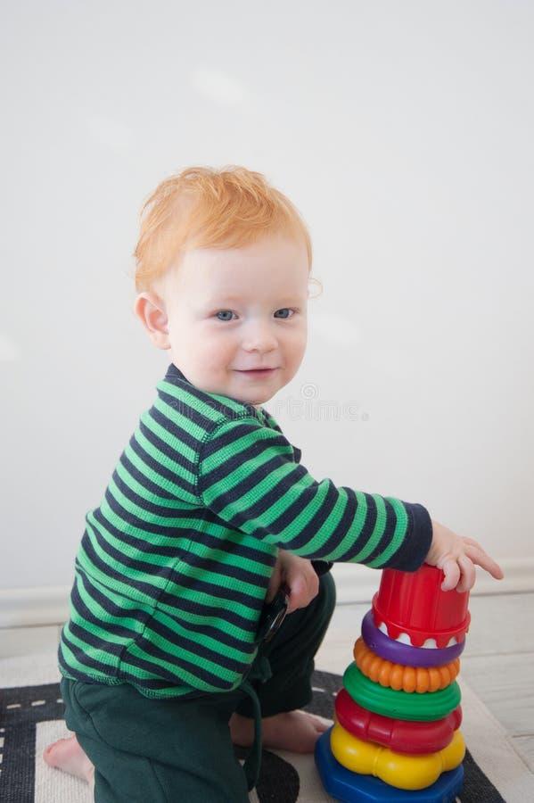 Röd pojke som spelar med en pyramid royaltyfria foton