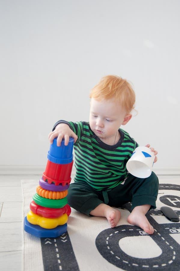 Röd pojke som spelar med en pyramid royaltyfri fotografi