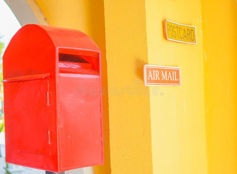 Röd postbox i gul bakgrund arkivbild