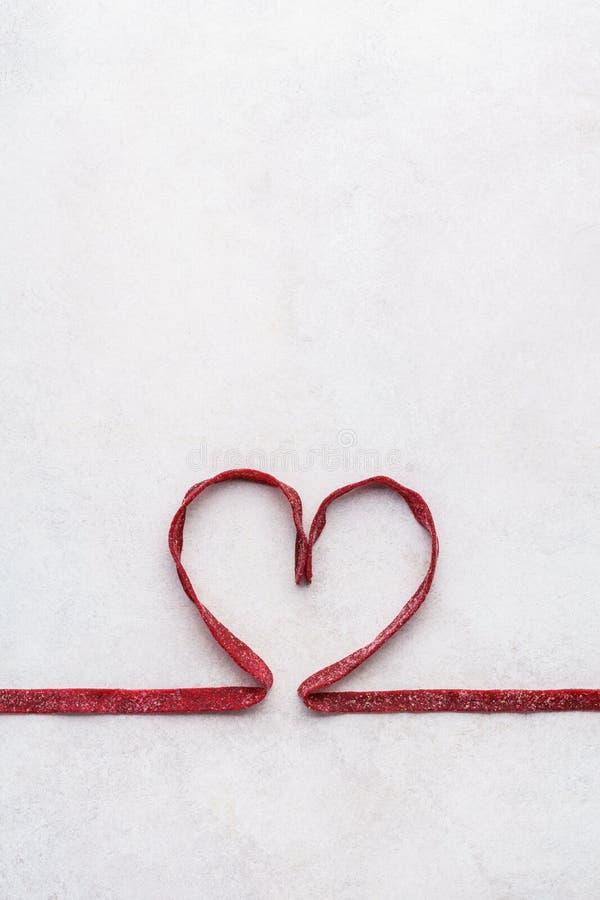 Röd rödbetapasta som formas som hjärta Bil för hälsning för dag för valentin` s arkivbilder