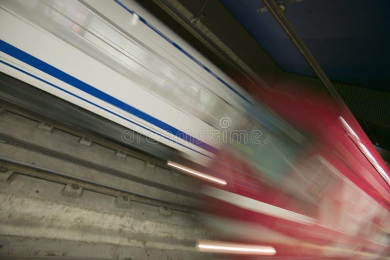 Röd rörelsesuddighet av att rusa drevet på stationen för tunnelbanagångtunneldrev i Madrid, Spanien royaltyfria foton