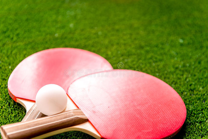 Röd racket för knackar upp slut för bakgrund för pongbollgräsplan arkivbilder