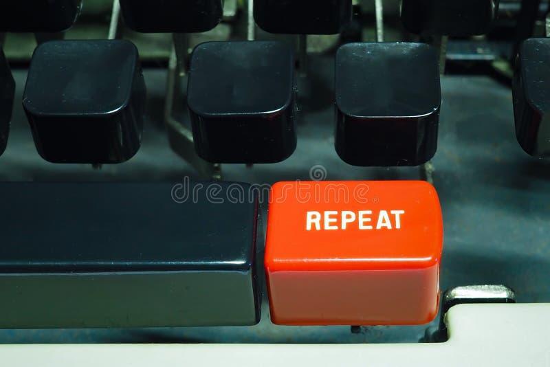 Röd repetitionknapp på skrivmaskinen Gör något igen arkivfoto