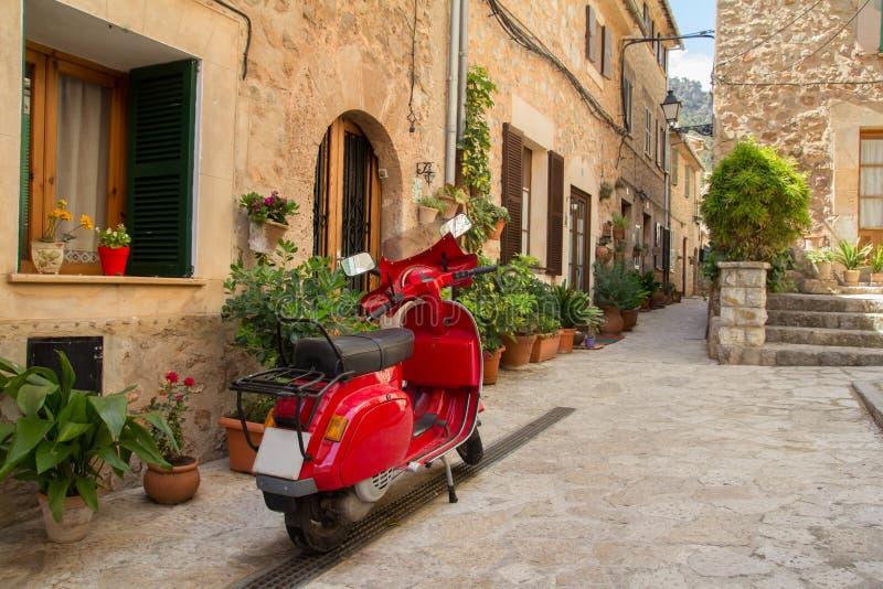 Röd retro sparkcykel som parkeras på gatan royaltyfri fotografi