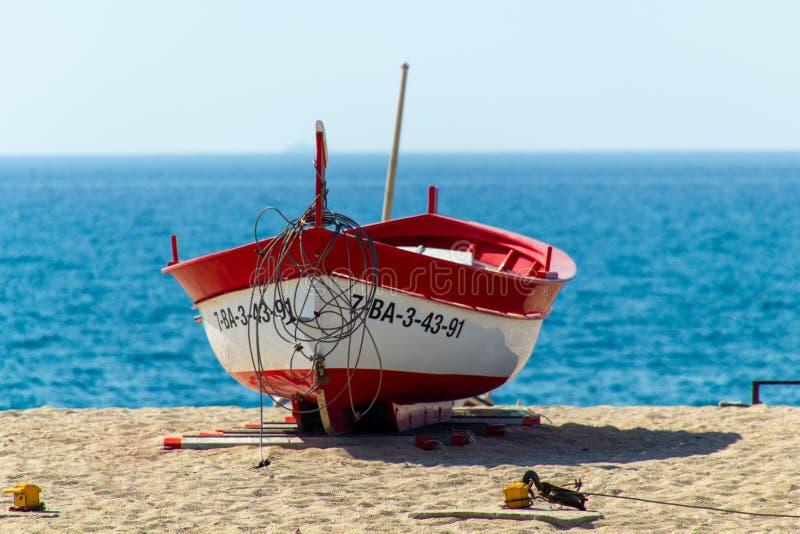 Röd roddbåt på sanden nära havet royaltyfri foto
