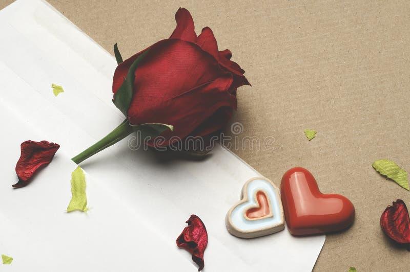 Röd ros i ett kuvert på ett ljus - brun bakgrund royaltyfri fotografi