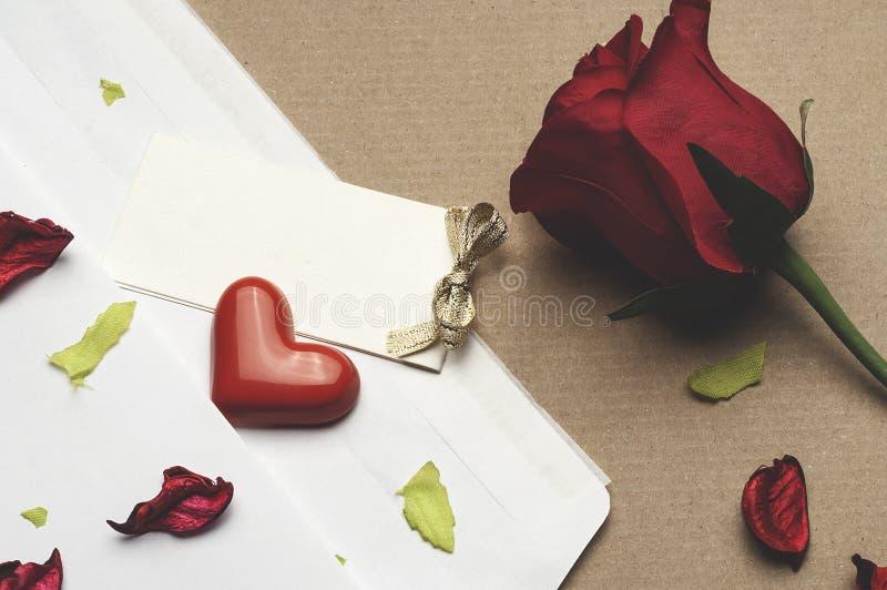 Röd ros i ett kuvert på ett ljus - brun bakgrund royaltyfria bilder