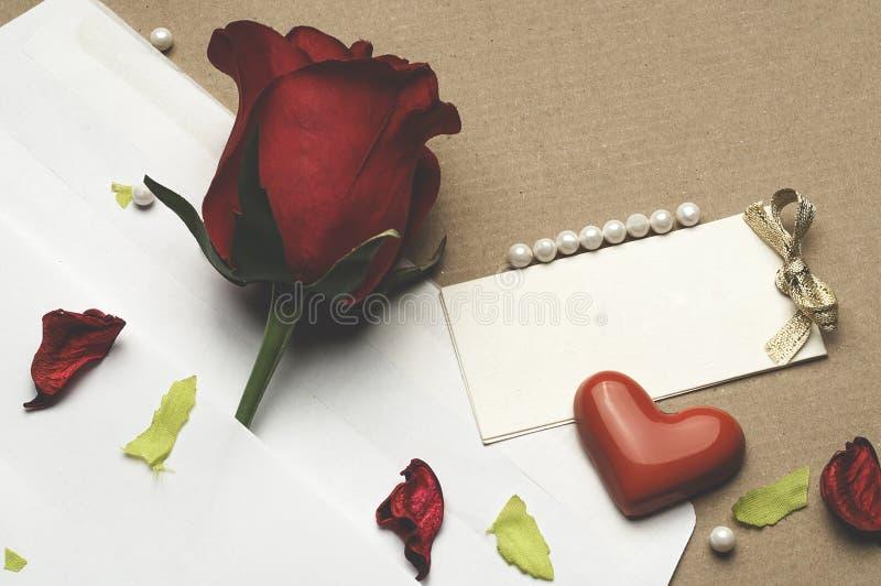 Röd ros i ett kuvert på ett ljus - brun bakgrund royaltyfri foto
