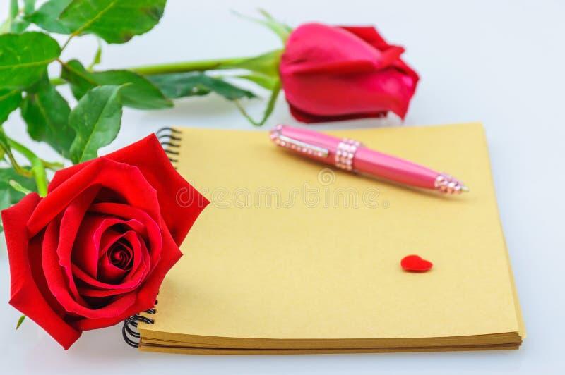 Röd ros- och rosa färgpenna med anteckningsboken Fotoet fokuseras på vänstersidan steg arkivfoton