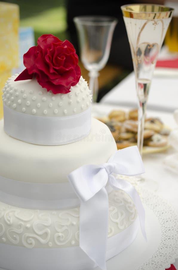 Röd ros på en bröllopstårta royaltyfri foto