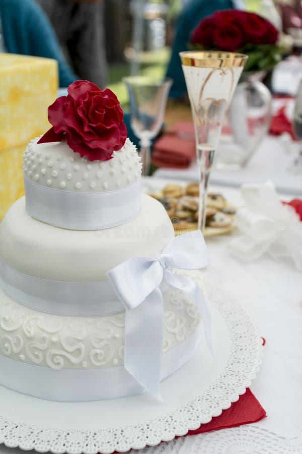 Röd ros på en bröllopstårta royaltyfri fotografi