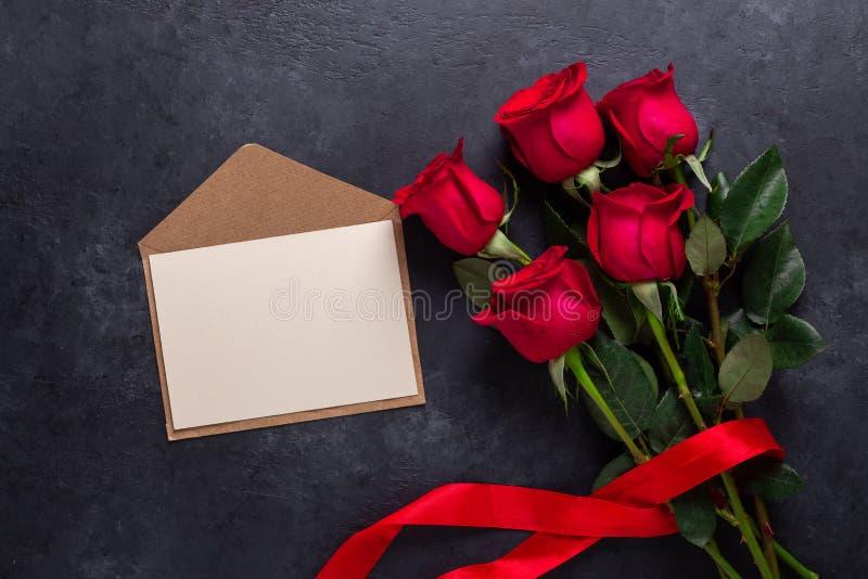 Röd rosa blommabukett och ett kuvert på svart stenbakgrundsvalentin kort för hälsning för dag fotografering för bildbyråer