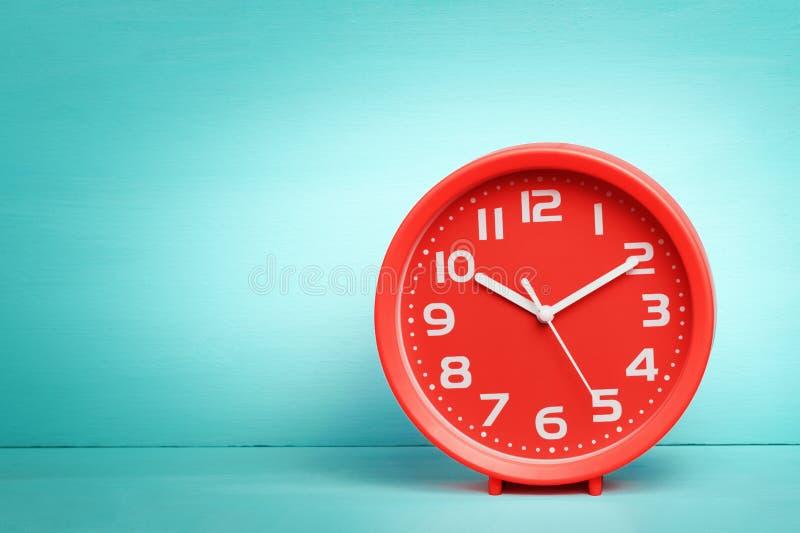 Röd rund klocka med vita pilar och nummer På tabellen bakgrund, vägg, färgblått, turkos royaltyfri fotografi