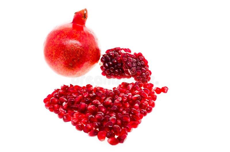 Röd saftig granatrött i form av en hjärta som isoleras på vit bakgrund arkivfoton