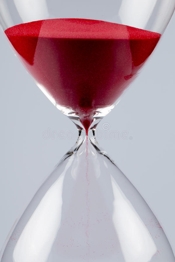 Röd sand i ett timglas, lodlinje arkivbilder