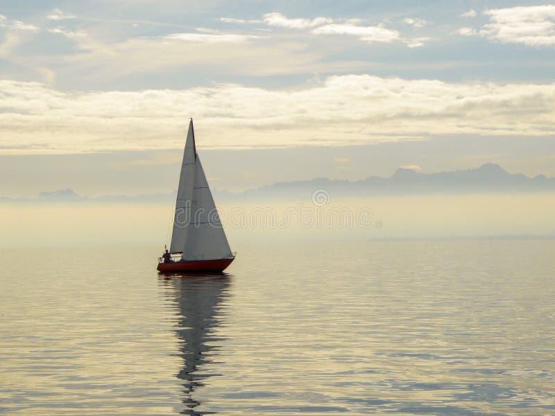 Röd segelbåt på sjön Constance Germany med schweiziska fjällängar i avståndet royaltyfri fotografi