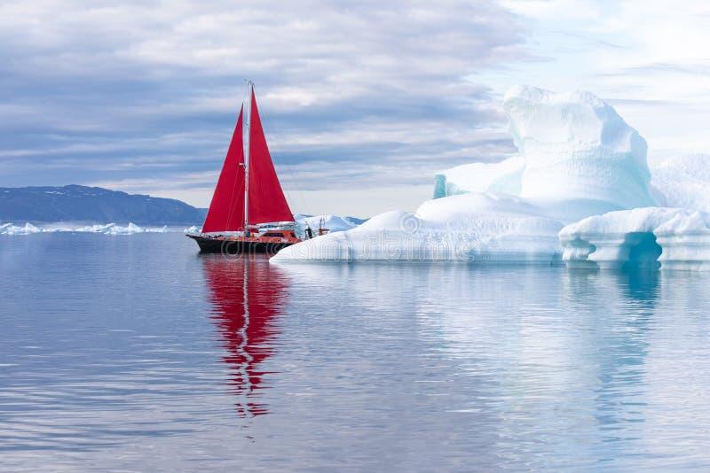 Röd segelbåt som kryssar omkring bland isberg royaltyfria bilder