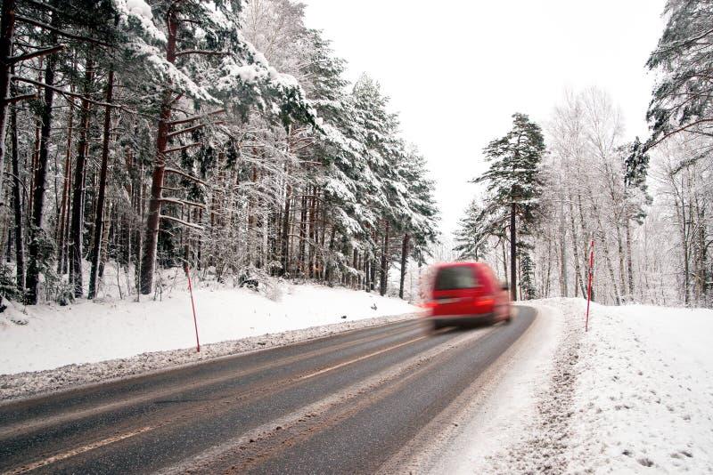 Röd skåpbil på vintervägen arkivfoto
