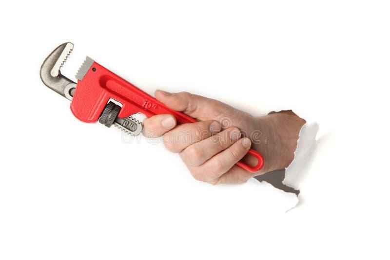 Röd skiftnyckel i hand på vit bakgrund royaltyfri foto
