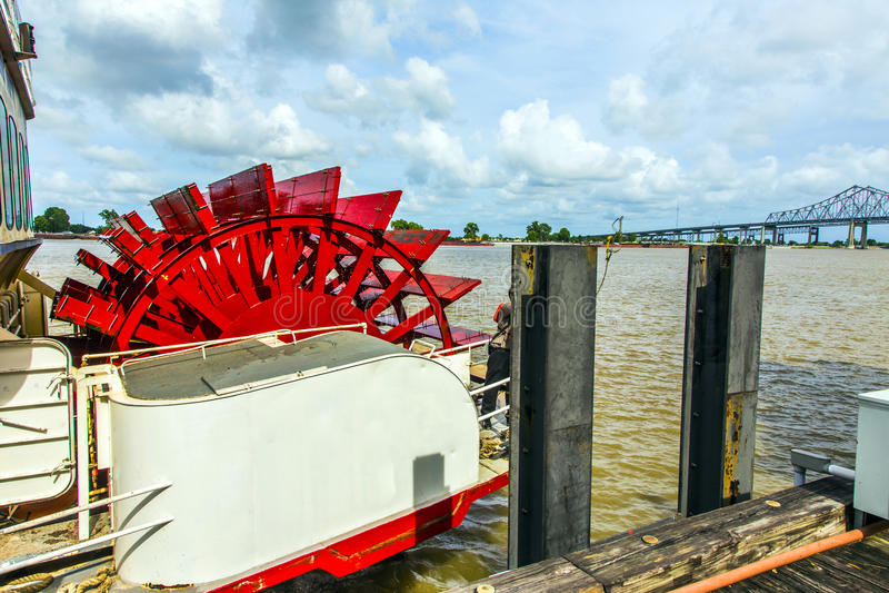 Röd skovelperson som drar en skottkärra på Mississippiet River royaltyfri bild