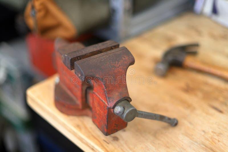 Röd skruvstäd på arbetsbänk med hammaren arkivfoto