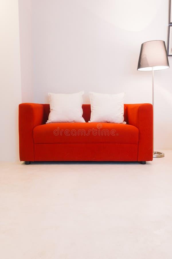Röd soffa med kudde- och ljuslampan arkivfoto