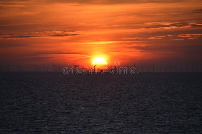 Röd solnedgång med windfarm på havet arkivbild