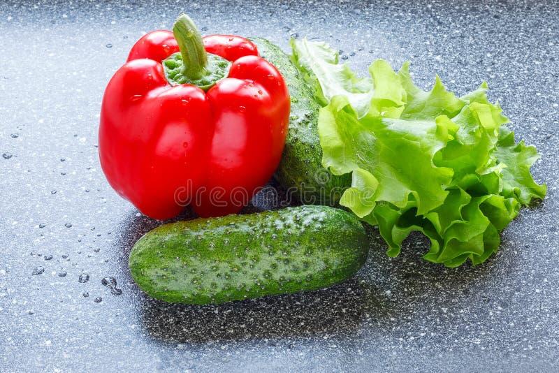 Röd spansk peppar, gurkor och grönsallat arkivbilder