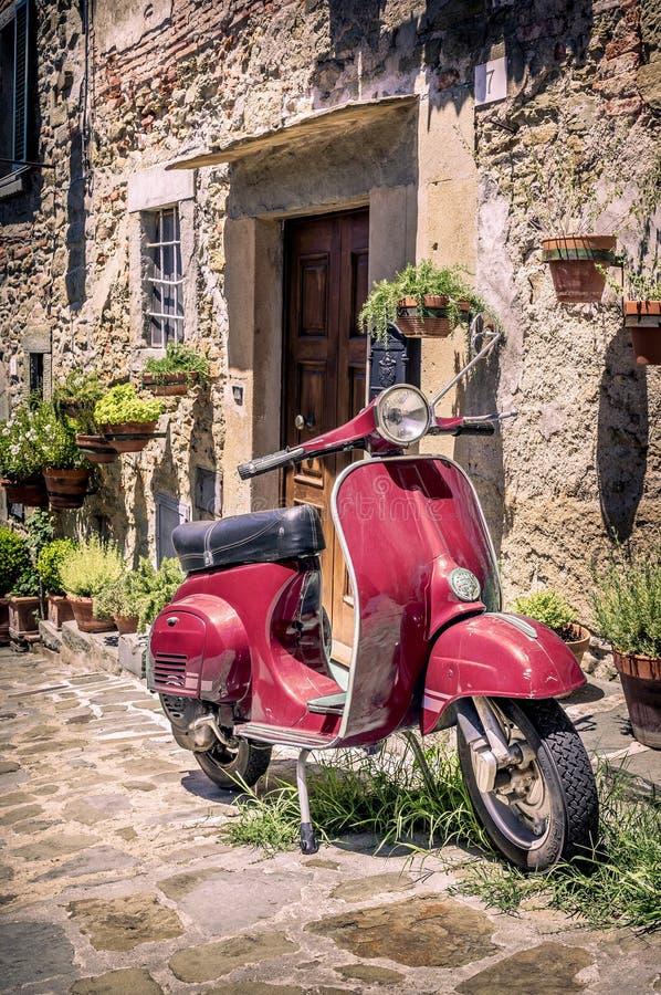 Röd sparkcykel i Tuscany royaltyfri bild