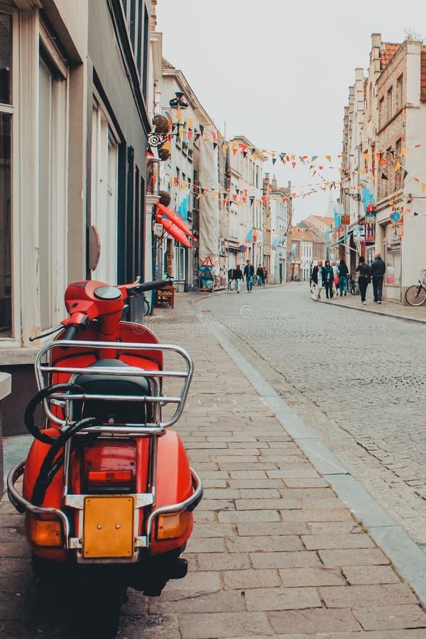 Röd sparkcykelmotocycle som parkeras på en gata i Belgien arkivbild