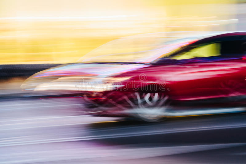 Röd sportbil i en suddig stadsplats royaltyfri bild