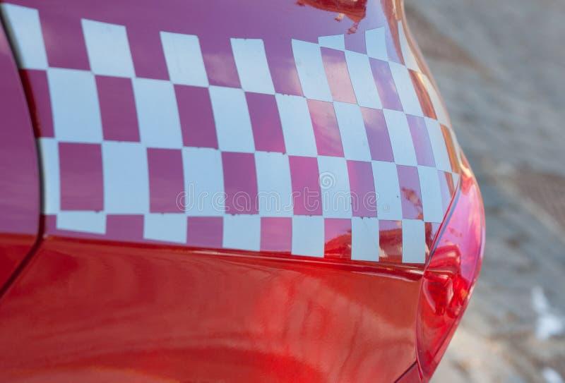 Röd sportbil med en rutig flaggagarnering royaltyfri bild