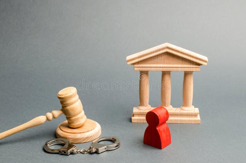 Röd statyett av en man på försöket Skydd av svarandet i kriminalfallet Skyddsstrategi dom på fallet royaltyfri fotografi