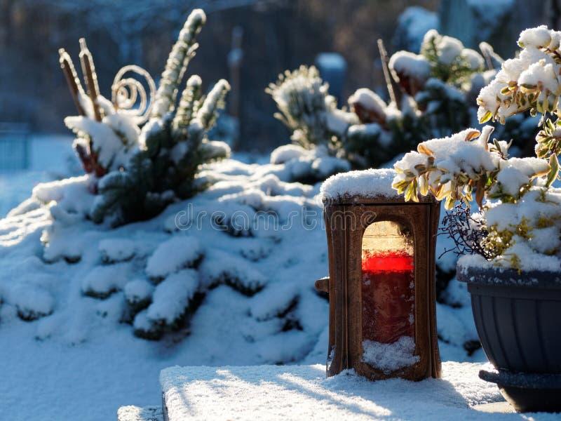 Röd stearinljus i snöig kyrkogård arkivfoto