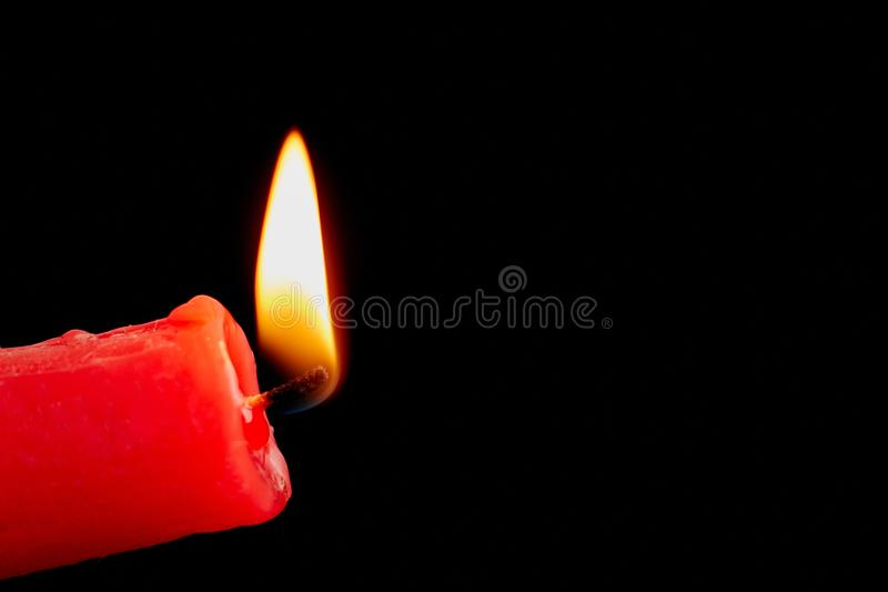 Röd stearinljus som isoleras på svart bakgrund arkivbilder