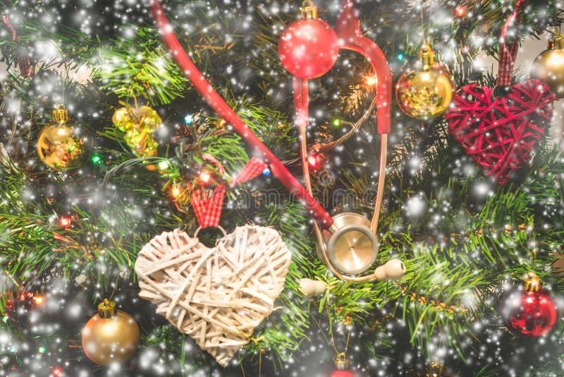 Röd stetoskop som hänger på en dekorerad julgran Medicinsk jul royaltyfria foton