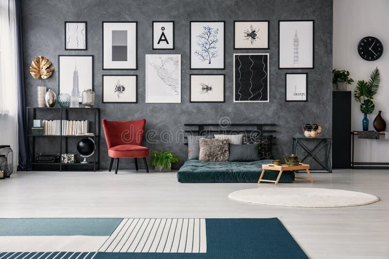 Röd stol bredvid grön futon med kuddar i grå lägenhetinre med affischer och filten Verkligt foto arkivfoto