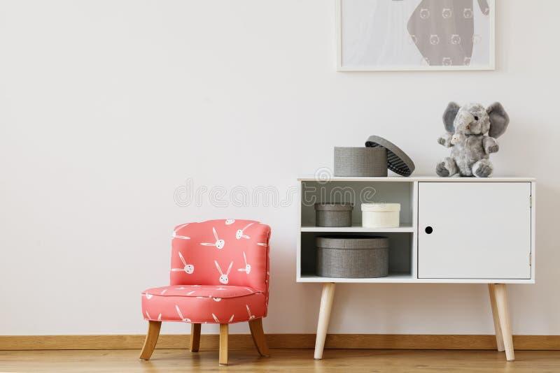 Röd stol med kaninmodellen arkivbilder