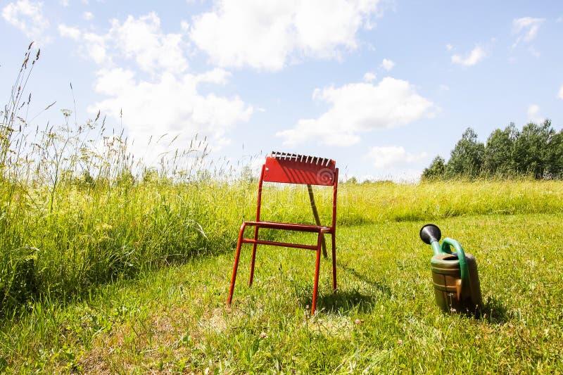 Röd stol och att bevattna kan på mejad sommaräng i bygd arkivbild