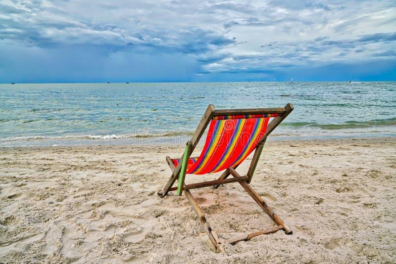 Röd stol som vänder mot havet på stranden royaltyfria bilder