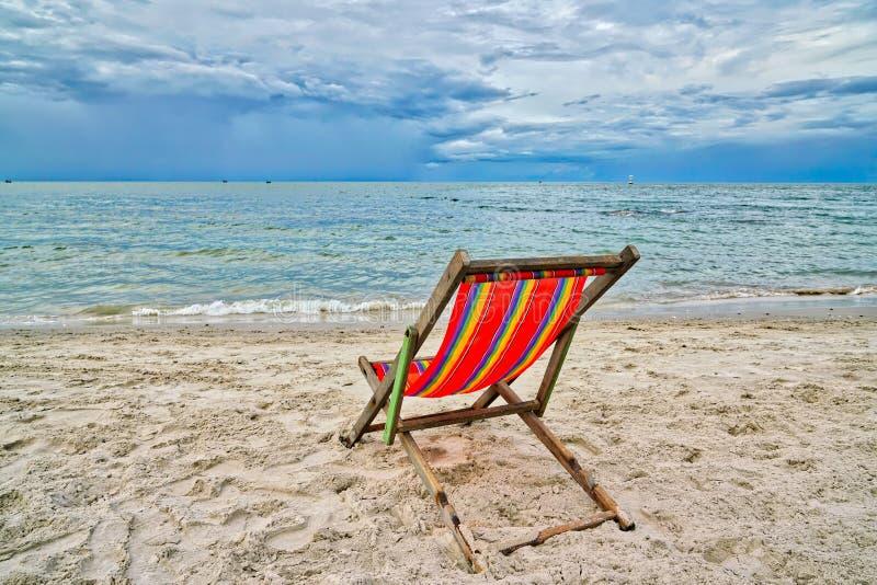 Röd stol som vänder mot havet på stranden royaltyfri bild