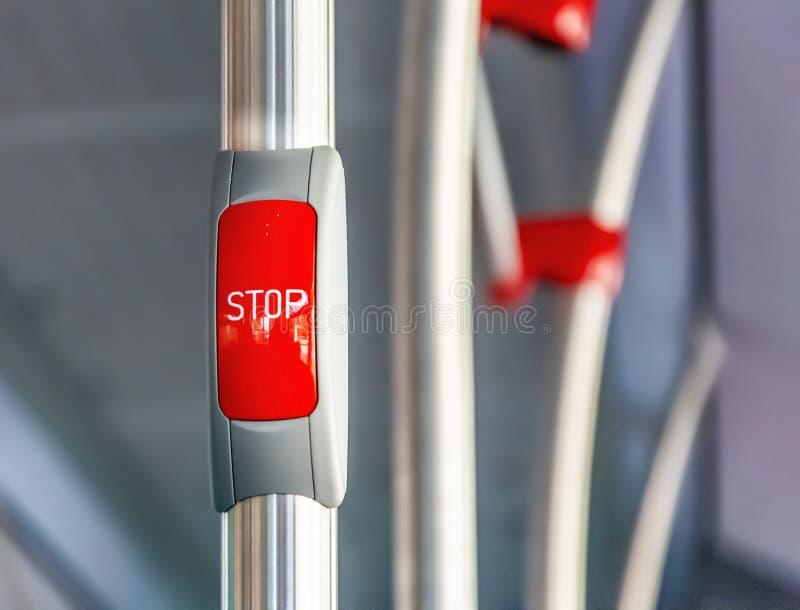 Röd stoppknapp på metallledstången av en buss arkivfoton