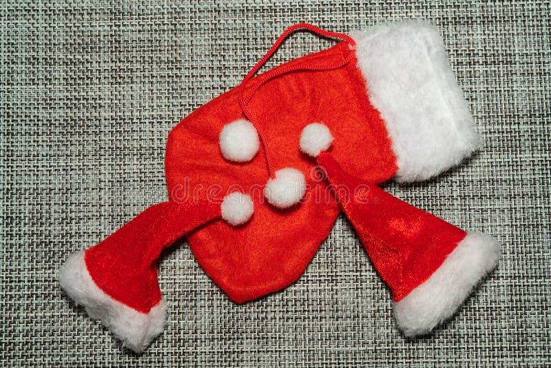 Röd strumpa för julgarnering och jultomtenhatt på grått bakgrundsslut upp royaltyfria bilder