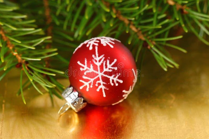 Röd struntsak för jul med snöflingaprydnaden på guld- bakgrund royaltyfria foton