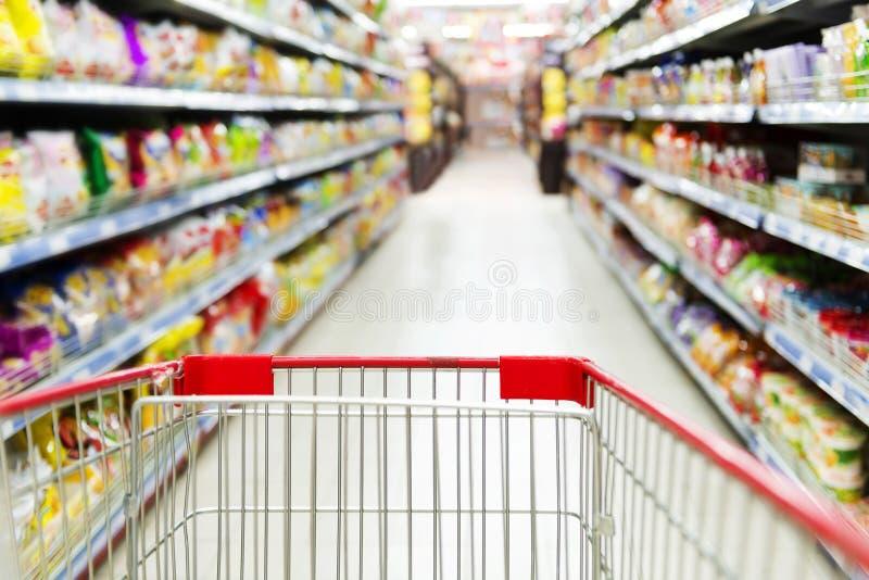 Röd supermarket inom den tomma shoppingvagnen royaltyfri foto