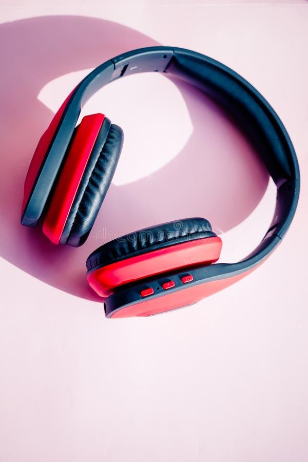 Röd svart trådlös hörlurar på rosa bakgrund och annonseringsområde som digital teknologi bluetooth och arkivfoto